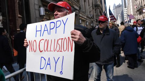 """A man holds a sign that reads """"Happy No Collusion Day"""" while people attend a rally in support of President Donald Trump near Trump Tower on March 23, 2019 in New York City."""
