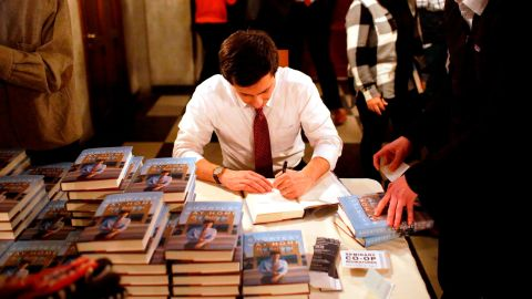 """Buttigieg signs copies of his book """"Shortest Way Home"""" in February 2019."""