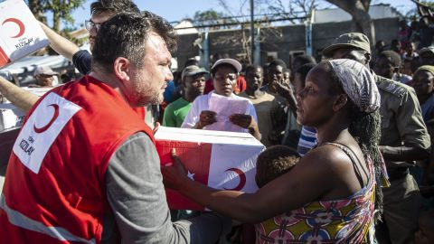 BEIRA, MOZAMBIQUE - MARCH 25: Mozambiqueans are seen as they receive humanitarian aid sent by Turkish aid agencies in Muabvi village of Beira, Mozambique province after Cyclone Idai hit the area on March 25, 2019. The shipment of food and cleaning materials, along with items from other relief agencies, was sent in containers via by ship to Beira, the area hardest hit by Cyclone Idai. (Photo by Gokhan Balci/Anadolu Agency/Getty Images)
