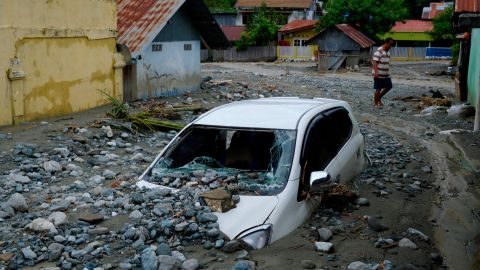 A car sits abandoned in the mud on a flooded street.