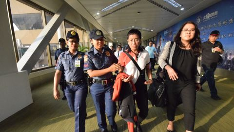 Philippine journalist Maria Ressa is escorted by police after an arrest warrant was served, shortly after arriving at the Ninoy Aquino International Airport in Manila.