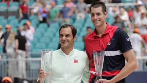 Roger Federer and John Isner pose with their trophies.