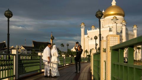 A newlywed couple pose for photographs at the Sultan Omar Ali Saifuddien mosque in Bandar Seri Begawan, on April 1, 2019.