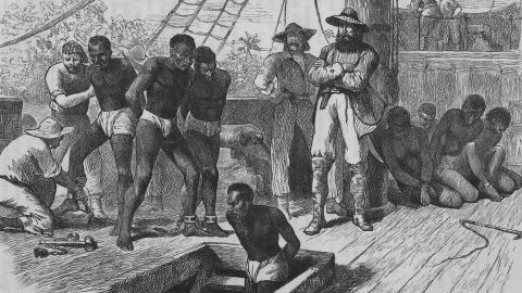 An illustration shows slaves being shackled on board a slave ship.