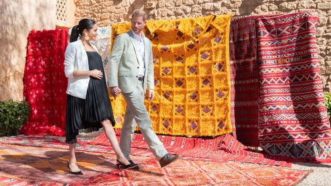 Meghan and Harry walk past tapestries during a visit to Rabat, Morocco, in February 2019.