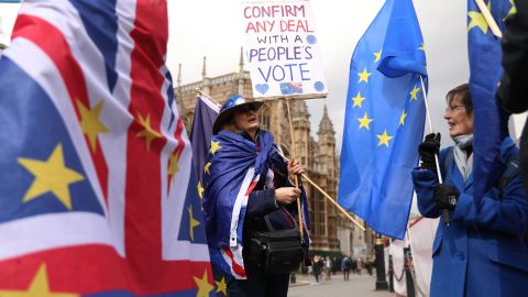"""A pro-EU campaigner holds the EU flag and displays placards near the Houses of Parliament in central London on April 3, 2019. - Prime Minister Theresa May was to meet Wednesday with Britain's main opposition party leader in a bid to forge a Brexit compromise that avoids a dreaded """"no-deal"""" departure from the EU in nine days. (Photo by ISABEL INFANTES / AFP)        (Photo credit should read ISABEL INFANTES/AFP/Getty Images)"""