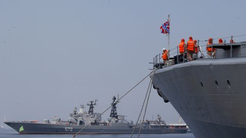 The crew of the Russian Navy destroyer Admiral Tributs secure their ship as the Russian destroyer Vinogradov, rear, prepares to dock at Manila's South Harbor Monday, April 8, 2019, in Manila, Philippines. Three ships from the Pacific Fleet of Russia, including Vinogradov and a large tanker Irkut, arrived Monday for a five-day goodwill visit to the country. Both Admiral Tributs and Vinogradov are classified as large anti-submarine ships. (AP Photo/Bullit Marquez)