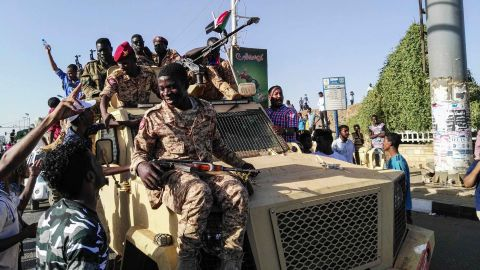 Protesters sit atop a military vehicle as soldiers stand nearby on April 7.