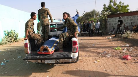 Sudanese soldiers transport a body near the military headquarters on Tuesday, April 9. The Central Committee of Sudan Doctors said 22 people, including five soldiers, had been killed in mass protests.