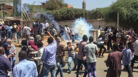 Protesters run for cover on April 6, as tear-gas canisters are fired by police.