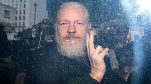 LONDON, ENGLAND - APRIL 11: Julian Assange gestures to the media from a police vehicle on his arrival at Westminster Magistrates court on April 11, 2019 in London, England.  After weeks of speculation Wikileaks founder Julian Assange was arrested by Scotland Yard Police Officers inside the Ecuadorian Embassy in Central London this morning. Ecuador's President, Lenin Moreno, withdrew Assange's Asylum after seven years citing repeated violations to international conventions. (Photo by Jack Taylor/Getty Images)