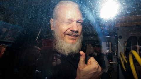 Julian Assange gestures to the media from a police vehicle on his arrival at Westminster Magistrates court on April 11, 2019 in London, England.  After weeks of speculation Wikileaks founder Julian Assange was arrested by Scotland Yard Police Officers inside the Ecuadorian Embassy in Central London this morning. Ecuador's President, Lenin Moreno, withdrew Assange's Asylum after seven years citing repeated violations to international conventions.