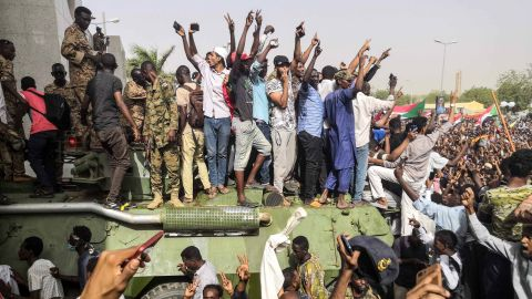 """Sudanese anti-regime demonstrators stand on an army armoured military vehicle on April 11, 2019 as they cheer and flash the sign of victory in the area around the army headquarters where protesters have held an unprecedented sit-in now in its sixth day in Sudan's capital Khartoum to call on their president to step down. - The Sudanese army is planning to make """"an important announcement"""", state media said today, after months of protests demanding the resignation of longtime leader President Omar al-Bashir. Thousands of Khartoum residents chanted """"the regime has fallen"""" as they flooded the area around the military headquarters."""