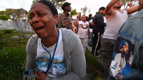 A woman cries as the hearse carrying the remains of rapper  Nipsey Hussle arrives at the funeral home.