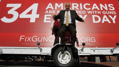 Booker leaps from the wheel cover of a mobile billboard after taking photos on it in February 2011. The truck was driven across the nation to draw attention to US gun laws.