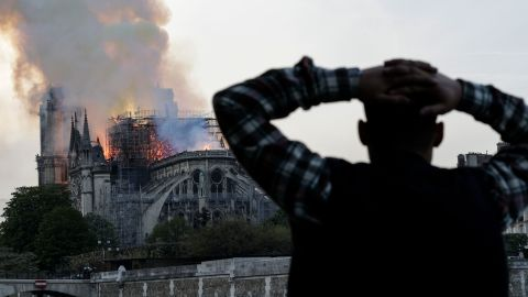 A man holds his head in shock as watches the fire take hold.