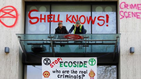 An activist sprays graffiti on an awning at the Shell Centre, offices of Royal Dutch Shell, as demonstrators surround the building during an environmental protest by Extinction Rebellion members on Monday, April 15.