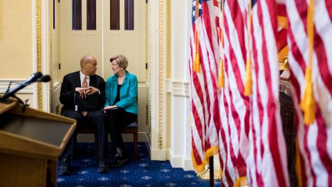 Booker and US Sen. Elizabeth Warren talk before the start of a July 2017 news conference that introduced the Dignity for Incarcerated Women Act.
