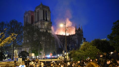 Crowds look on as flames and smoke billow from the roof at Notre-Dame Cathedral in Paris on April 15, 2019. - A fire broke out at the landmark Notre-Dame Cathedral in central Paris, potentially involving renovation works being carried out at the site, the fire service said.Images posted on social media showed flames and huge clouds of smoke billowing above the roof of the gothic cathedral, the most visited historic monument in Europe. (Photo by ERIC FEFERBERG / AFP)