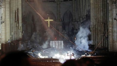 Smoke rises in front of the altar cross at Notre-Dame Cathedral in Paris on April 15, 2019, after a fire engulfed the building. - A huge fire swept through the roof of the famed Notre-Dame Cathedral in central Paris on April 15, 2019, sending flames and huge clouds of grey smoke billowing into the sky. The flames and smoke plumed from the spire and roof of the gothic cathedral, visited by millions of people a year. A spokesman for the cathedral told AFP that the wooden structure supporting the roof was being gutted by the blaze. (Photo by PHILIPPE WOJAZER / POOL / AFP)        (Photo credit should read PHILIPPE WOJAZER/AFP/Getty Images)