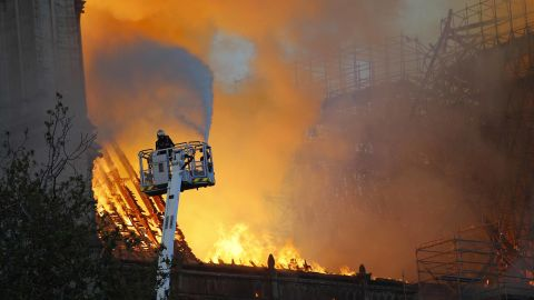 A firefighter uses a hose to tackle the flames as the cathedral's roof burns.