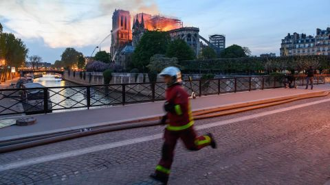 Flames and smoke rise from Notre Dame as a firefighter rushes past.
