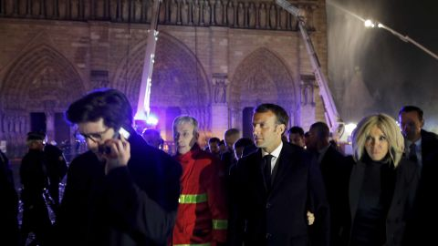 French President Emmanuel Macron, center, and his wife Brigitte at the scene of the fire on Monday evening.