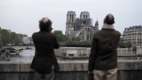 People stop to view Notre Dame Cathedral on the morning following the fire.