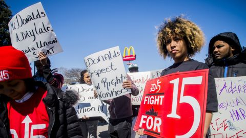 Detroit resident Betty Killingsworth, right, stands tall with a few dozen cooks and cashiers marching throughout the parking lot on Wednesday, April 3, 2019, during a rally at McDonald's in the 1500 block of W. Stewart Avenue in Flint, demanding a $15 hourly minimum wage increase, union rights and calling on the company not to just stop lobbying against them, but join in the request for a higher minimum wage. Protestors gathered at 10 total locations around the nation, including Chicago, Los Angeles and Memphis, among others. (Jake May/The Flint Journal via AP)