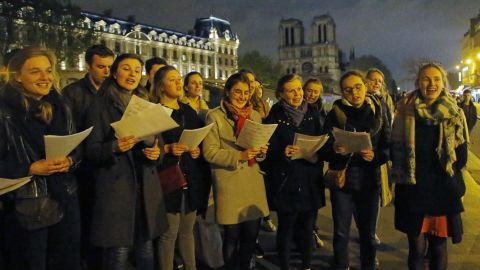 People attend a vigil near the Notre Dame cathedral in Paris on Tuesday.