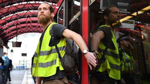 A climate change protester who glued his hand to a window halts a train at Canary Wharf station on Wednesday.