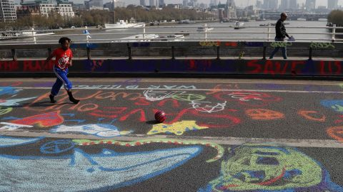 A boy plays football across chalk drawings during the ongoing blockade of Waterloo Bridge.