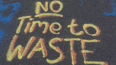 """""""No Time to Waste"""" is written on the pavement at Waterloo Bridge."""