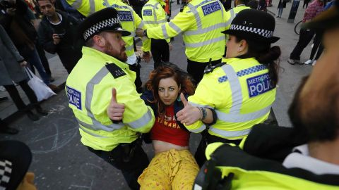TOPSHOT - Police carry away a climate change activist protesting at Oxford Circus on the third day of an environmental protest by the Extinction Rebellion group, in London on April 17, 2019. (Photo by Tolga AKMEN / AFP)        (Photo credit should read TOLGA AKMEN/AFP/Getty Images)