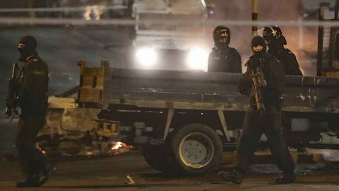 Police patrol the scene during Thursday night's violence.
