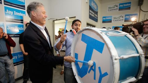 Inslee, running for governor, bangs on a drum while celebrating early election returns in 2012.