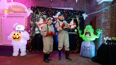 """Inslee and his wife -- dressed in costumes from the """"Ghostbusters"""" movies -- spray silly string as they greet trick-or-treaters at the governor's mansion in October 2016."""