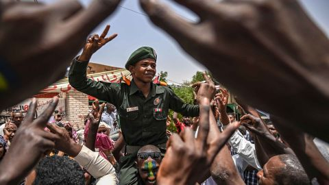 Protesters shout slogans as they carry a soldier flashing the victory sign outside the army headquarters on April 18.
