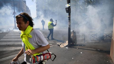 Protesters take cover from tear gas during an anti-government demonstration in Paris.