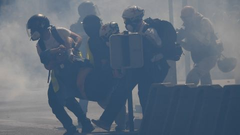 """So-called """"street medics"""" carry an injured protester amid tear gas."""