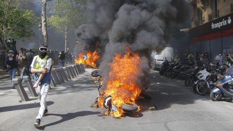 A man runs by a burning motorbike during a yellow vest demonstration in Paris on April 20, 2019.