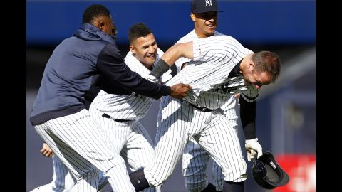 New York Yankees' Austin Romine, right, is congratulated by teammates after hitting a walk off single in the 10th inning against the Kansas City Royals on Sunday, April 21, in New York.