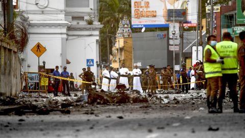 Sri Lankan priests look at the debris of a car after it explodes when police tried to defuse a bomb near St. Anthony's Shrine a day after the Easter Sunday  attacks.