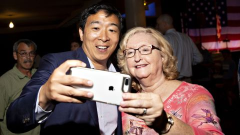 In August 2018, Yang takes a selfie with an attendee of the Democratic Wing Ding event in Iowa.