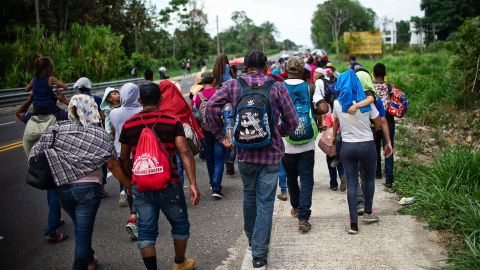 """Central American migrants heading to the US walk in caravan along the road between Metapa and Tapachula in Mexico on April 12, 2019. - A group of 350 Central American migrants forced their way into Mexico Friday, authorities said, as a new caravan of around 2,500 people arrived -- news sure to draw the attention of US President Donald Trump. Mexico's National Migration Institute said some members of the caravan had a """"hostile attitude"""" and had attacked local police in the southern town of Metapa de Dominguez after crossing the border from Guatemala. (Photo by PEP COMPANYS / AFP)        (Photo credit should read PEP COMPANYS/AFP/Getty Images)"""