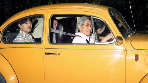 Akihito drives to an imperial villa in 1989. Michiko is in the front passenger seat. Behind Akihito is his son Fumihito.