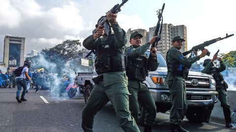Members of the military who support Guaido fire into the air to repel forces loyal to Maduro on Tuesday, April 30. The Maduro forces were trying to disperse a demonstration near the La Carlota base.