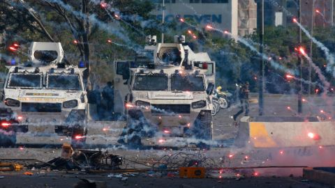 Fireworks launched by opponents of Venezuela's President Nicolas Maduro land near Bolivarian National Guard armored vehicles loyal to Maduro, during an attempted military uprising in Caracas, Venezuela, Tuesday, April 30, 2019. Opposition leader Juan Guaido took to the streets with a small contingent of heavily armed troops in a call for the military to rise up. (AP Photo/Ariana Cubillos)