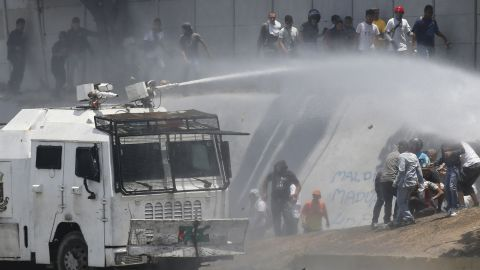 A Bolivarian National Guard water canon sprays opponents of Venezuela's President Nicolas Maduro during an attempted military uprising and anti-government protests in Caracas, Venezuela, Tuesday, April 30, 2019. Venezuelan opposition leader Juan Guaido and jailed opposition leader Leopoldo Lopez took to the streets with a small contingent of heavily armed troops early Tuesday in a bold and risky call for the military to rise up and oust Maduro.