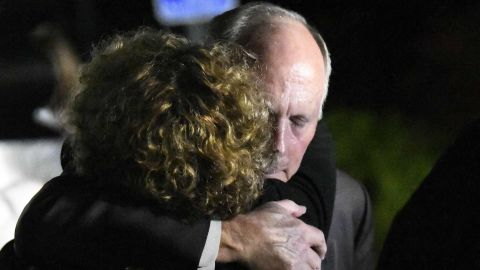 UNC Charlotte Chancellor Philip Dubois receives a hug after a news conference on the deadly shooting.